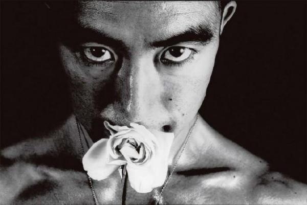 三岛由纪夫嘴里叼着一朵蔷薇花的特写